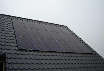 Een detailfoto van het dak waar 24 zonnepanelen op liggen
