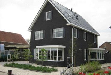 Zwarte hoogbouw woning met erker en aanbouw
