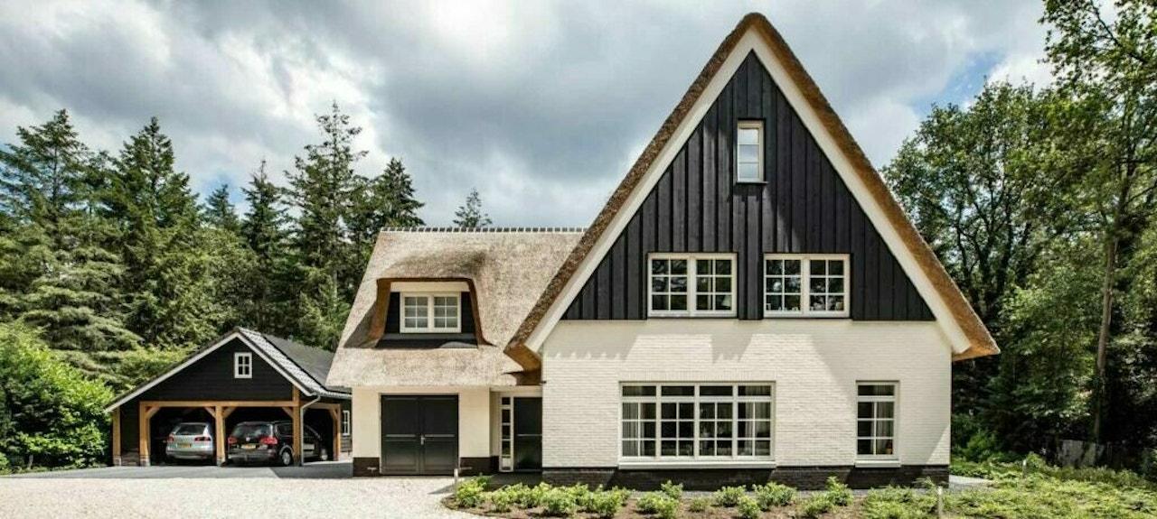 En zwart-wit statig landhuis met een landelijke uitstraling en rieten kap