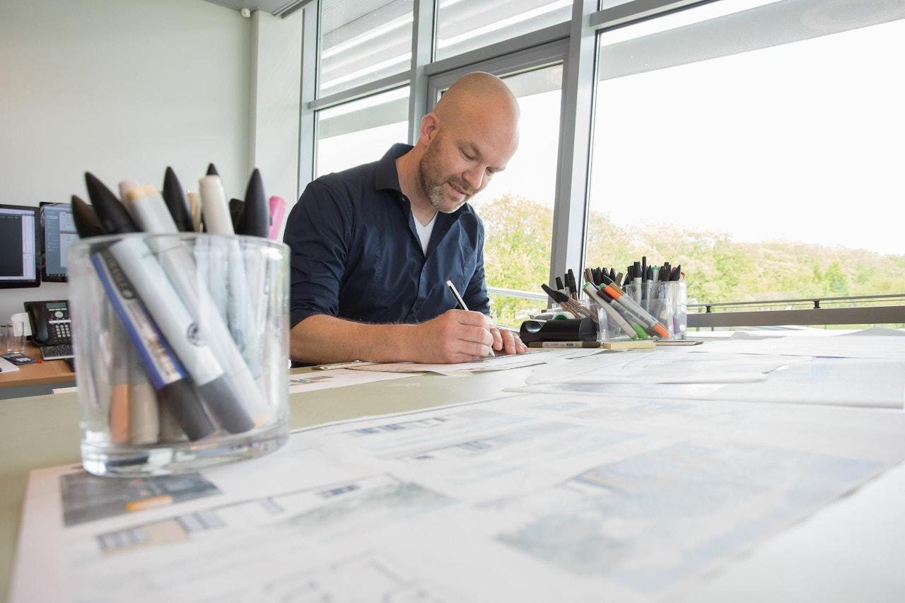 Een medewerker van de tekenkamer werkt aan een schetsontwerp