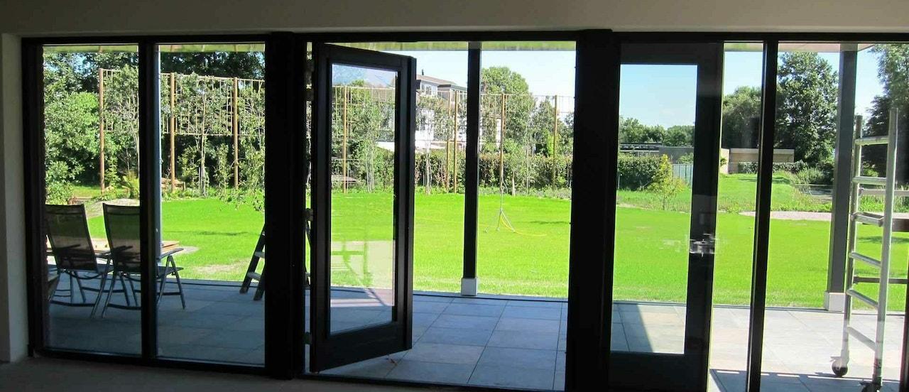 Door de tuindeuren is de veranda zichtbaar met daarachter het uitzicht op de tuin