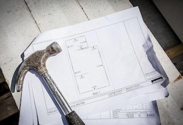 Bouwtekening met een hamer op de bouwplaats