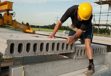 Bouwvakker die een betonnen vloerplaat plaatst