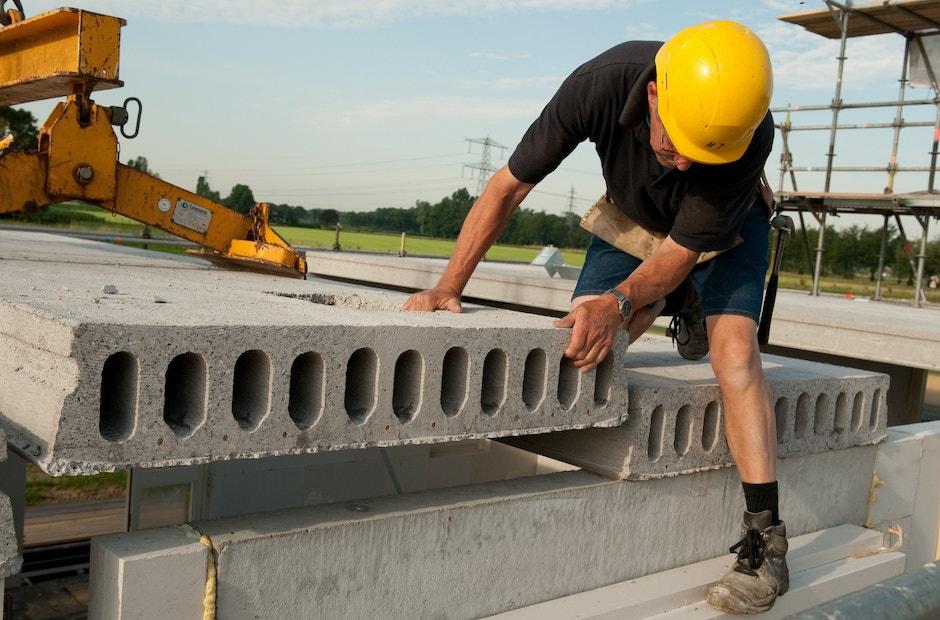 Bouwvakker plaatst betonnen vloerplaat