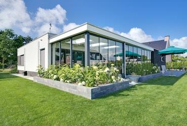 Achteraanzicht van een witte bungalow met overdekt terras