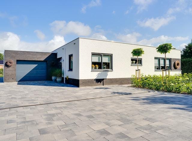 Vooraanzicht van een witte bungalow met zwarte garage