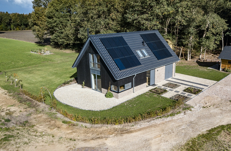 Luchtfoto van een zwarte schuurwoning met zonnepanelen