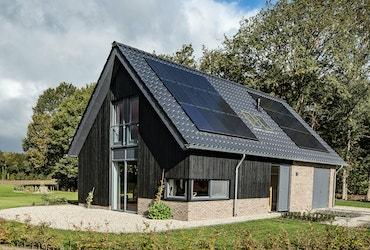 Vooraanzicht van een zwarte schuurwoning met zonnepanelen