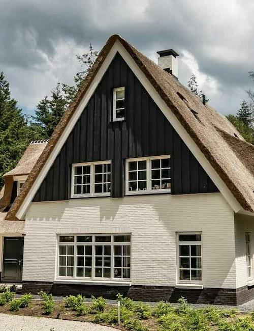 Vooraanzicht van een witte landelijke woning met rieten kap