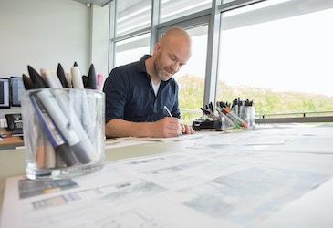 Tekenaar van SelektHuis achter zijn bureau